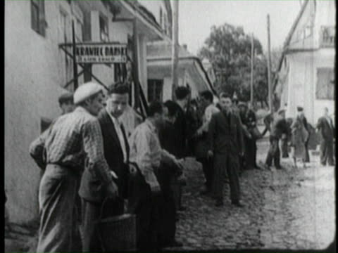 vídeos de stock, filmes e b-roll de aerial views of burning buildings in danzig after german invasion / citizens in streets helping out after bombing of warsaw people in street with... - polônia