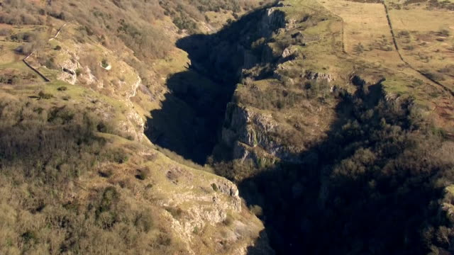 aerial views of cheddar gorge in the mendip hills, including shots of vehicles driving along the winding road at the bottom of the gorge.>> on... - cheddar gorge stock videos & royalty-free footage