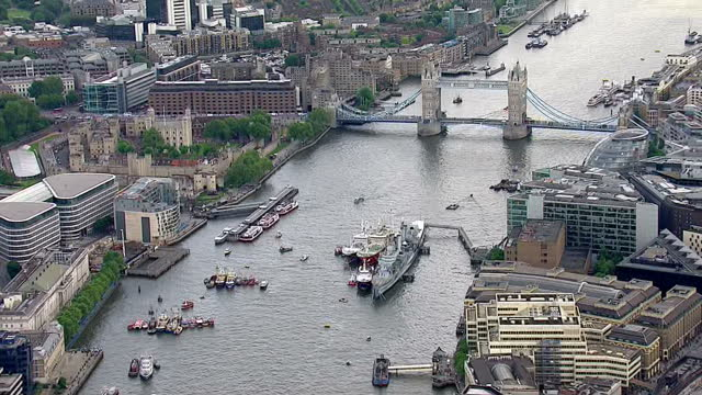 aerial views of fishing boat decorated in union flags moving down the river thames zoom into fishing vessel moored next to hms belfast with a banner... - 2016 european union referendum stock videos and b-roll footage