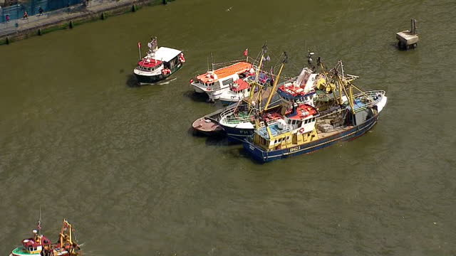 aerial views of fishing for leave boats moving down the river thames with banners reading the only way is brexit on june 15 2016 in london united... - 2016 european union referendum stock videos and b-roll footage