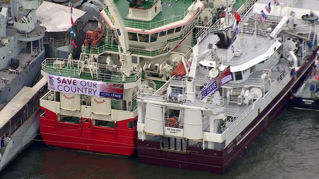 aerial views of fishing for leave eu referendum campaign boat moored next to hms belfast pan to 'in' campaign boats circling around in the river... - 2016 european union referendum stock videos and b-roll footage