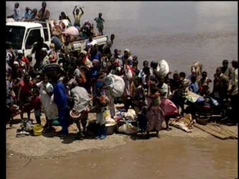 vídeos de stock e filmes b-roll de aerial views of flooded town and stranded people on rooftops / south african military helicopters rescuing people / flood victims wade through water... - moçambique