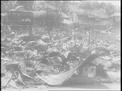 aerial views of honolulu / japanese planes fly overhead / hawaiian women read newspaper / bomb damaged houses and stores in city / men begin cleanup - 真珠湾攻撃点の映像素材/bロール