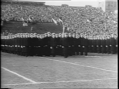 aerial views of philadelphia municipal stadium / naval cadets in formation on field / long shot of crowd in stands / illustration of navy goat mascot... - 士官候補生点の映像素材/bロール