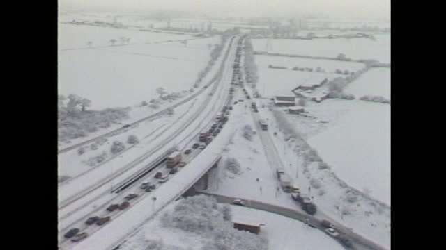 aerial views of queues of traffic stuck in snow during arctic blizzard across the uk in january 1987. - weather stock videos & royalty-free footage