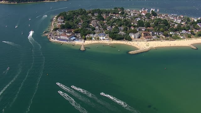 aerial views of sandbanks , a small peninsula or spit crossing the mouth of poole harbour on the english channel coast at poole in dorset on august... - bournemouth england stock videos & royalty-free footage