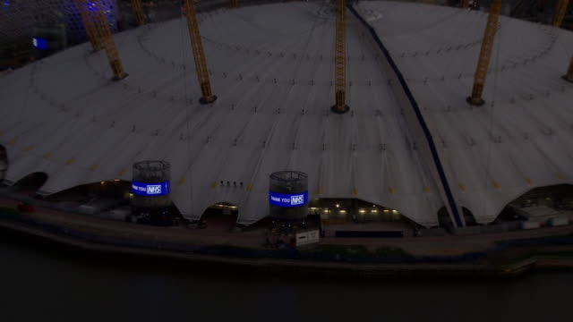 aerial views of the o2 lit up in support of the nhs and medical workers keeping us safe during the coronavirus epidemic on 2nd april 2020 london,... - the o2 england stock videos & royalty-free footage