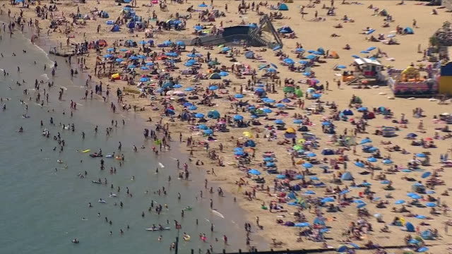 aerial views of thousands of people sunbathing, swimming and enjoying the heatwave on bournemouth beach next to bournemouth pier. on august 03, 2018... - bournemouth england stock videos & royalty-free footage