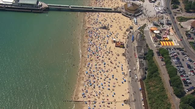 aerial views of thousands of people sunbathing swimming and enjoying the heatwave on bournemouth beach next to bournemouth pier on august 03 2018 in... - bournemouth england stock videos & royalty-free footage