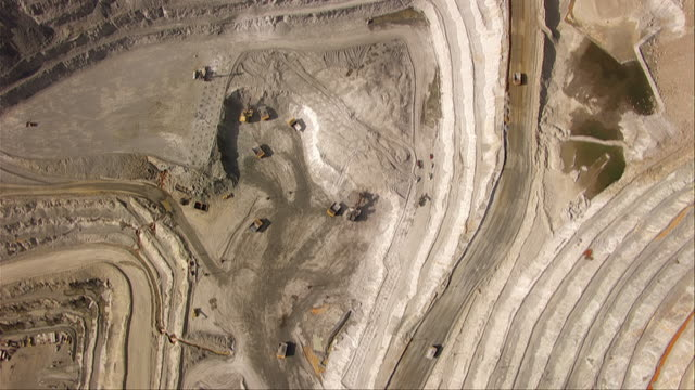 vídeos de stock e filmes b-roll de aerial views of trucks and diggers working in bingham canyon mine - metal