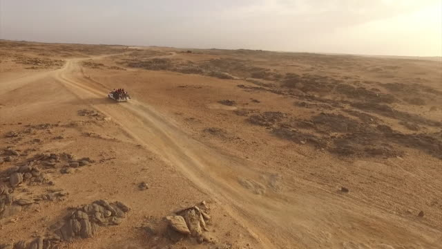 aerial views of trucks carrying migrants across the sahara in an attempt to reach the border between libya and niger - ニジェール点の映像素材/bロール