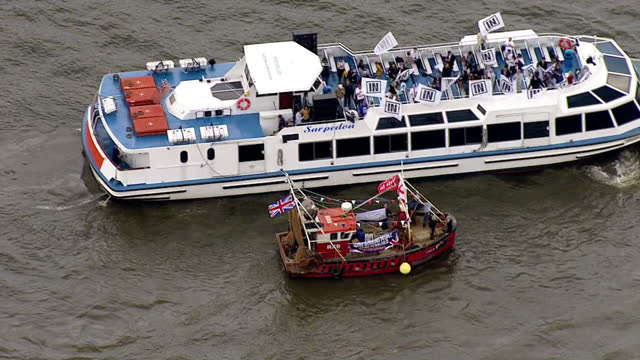 aerial views of vote leave campaigners in fishing vessels circling around vote remain campaign boat on the river thames outside of the houses of... - 2016 european union referendum stock videos and b-roll footage