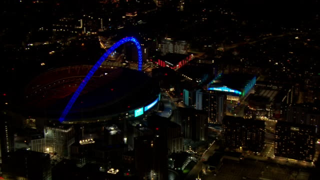 aerial views of wembley stadium and the sse arena lit up in support of the nhs and medical workers keeping us safe during the coronavirus epidemic on... - wembley stock videos & royalty-free footage