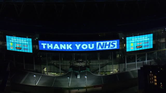 aerial views of wembley stadium lit up at night with thank you message to the nhs during coronavirus epidemic on 23th march 2020 london united kingdom - thank you englischer satz stock-videos und b-roll-filmmaterial