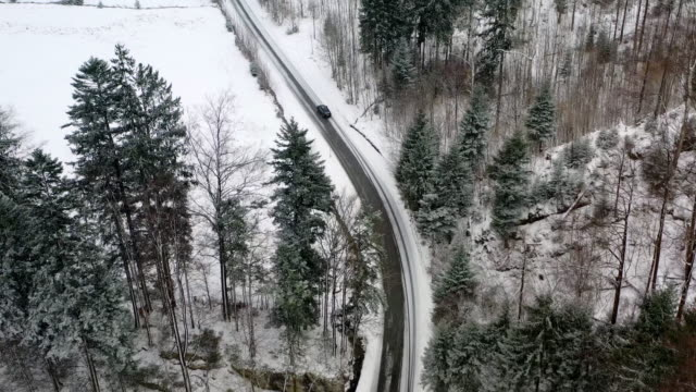 aerial views of winding wintery road following a car in bad weather with heavy snowfall - winding road stock videos & royalty-free footage