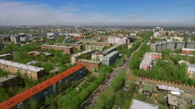aerial views show vast numbers of people attending an immortal regiment parade in irkutsk honouring those who died in wwii, russia. - ve day stock-videos und b-roll-filmmaterial