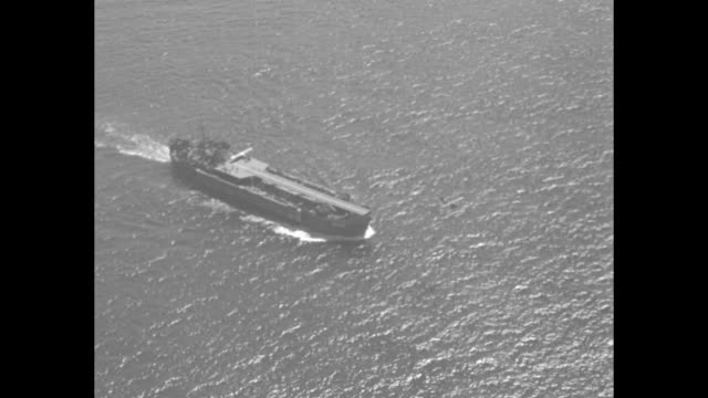 VS USS LST906 at sea plane takes off / VS on deck planes takes off / aerial planes in air over fleet of ships on sea / planes fly over lines of ships...