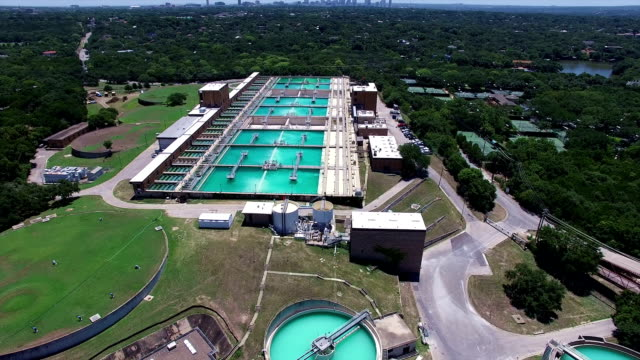aerial: water treatment purification plant high above the texas hill country next to the colorado river - sewage treatment plant stock videos & royalty-free footage