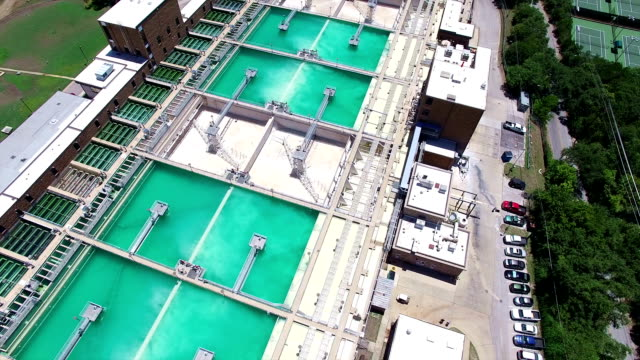 Aerial: Water Treatment Purification Plant looking down directly over Water storage