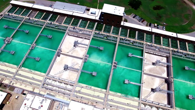 Aerial: Water Treatment Purification Plant pan across water cleaning storage compartments