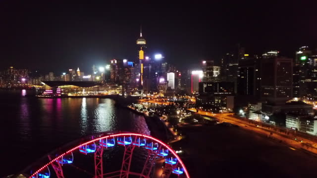 vídeos de stock e filmes b-roll de aerial: waterfront at night with hong kong observation wheel lit up in front - central plaza hong kong