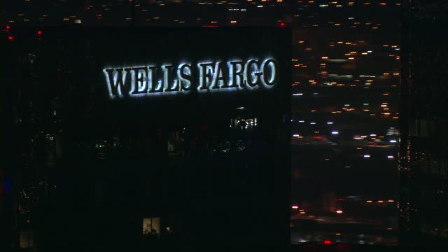 aerial ecu wells fargo sign on skyscraper, at night /  los angeles, california, united states. - wells fargo stock videos and b-roll footage