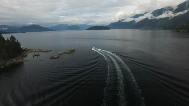aerial: white boat moving across wide lake with mountains behind - nautical vessel stock videos & royalty-free footage