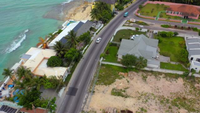 aerial: white car driving along waterfront road past tropical beach homes - nassau, bahamas - nassau stock videos & royalty-free footage