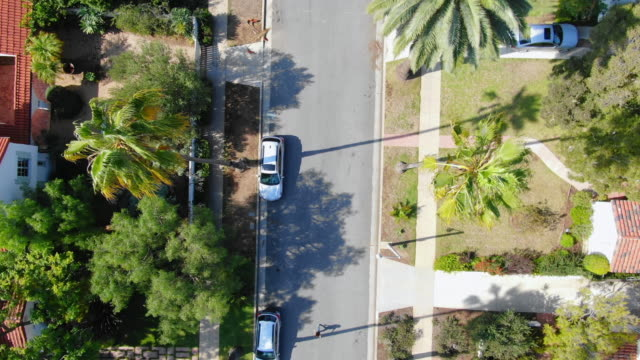 aerial: white car parked on street in santa monica neighborhood - santa monica, california - santa monica house stock videos & royalty-free footage