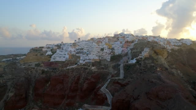 aerial: white homes on the top of a bluff in santorini, greece - gebäudefries stock-videos und b-roll-filmmaterial