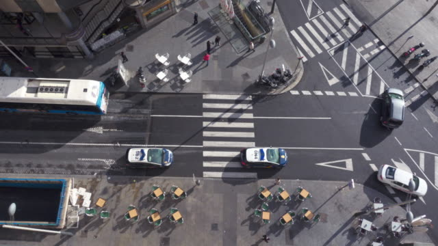 4K | Aerial wide angle shot of a crosswalk. Fluid traffic in this intersection of Madrid. Pedestrians cross the street. We can see the afternoon lateral shadows of the people and the cars. There are also tables and chairs of a bar restaurant terrace.