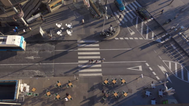 4k | aerial wide angle shot of a crosswalk. fluid traffic in this intersection of madrid. pedestrians cross the street. we can see the afternoon lateral shadows of the people and the cars. there are also tables and chairs of a bar restaurant terrace. - zebra crossing stock videos & royalty-free footage
