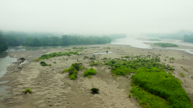aerial: wide sandy bank stretches across amazon river between jungle banks in dense fog - breit stock-videos und b-roll-filmmaterial