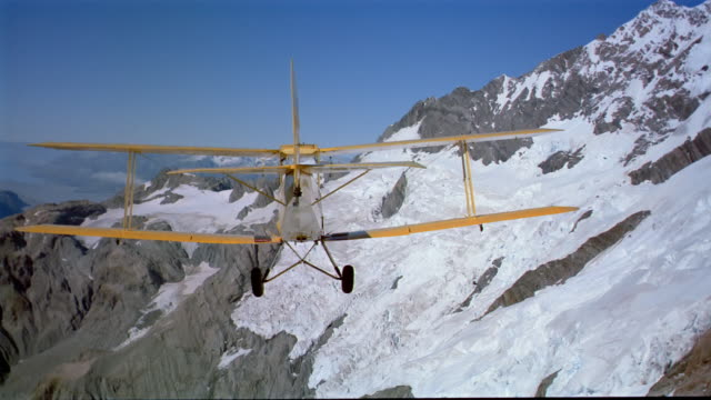 aerial wide shot biplane flying over snowcapped mountains / making loop / new zealand - flugzeug in der luft stock-videos und b-roll-filmmaterial