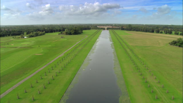 aerial wide shot canal in field leading up to hampton court palace / overhead gardens and palace / surrey, england - richmond upon thames stock-videos und b-roll-filmmaterial