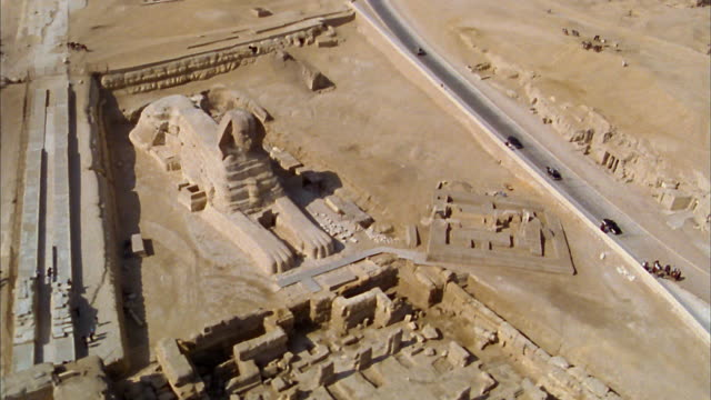 Aerial wide shot circling Great Sphinx of Giza in desert / Egypt