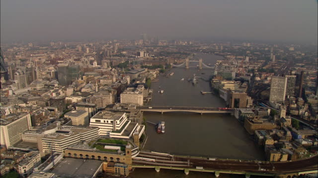 Aerial wide shot down Thames with view of Tower, London, Cannon Street Railway, and Southwark bridges and surrounding cityscape / London