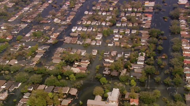 vídeos de stock, filmes e b-roll de aerial wide shot flooded gentilly subdivision / zoom in rescuers in inflatable dinghy / new orleans low angle - 2005