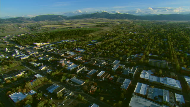 vidéos et rushes de aerial wide shot forward pov passing over main street in bozeman, mt then looking south toward distant mountains - montana