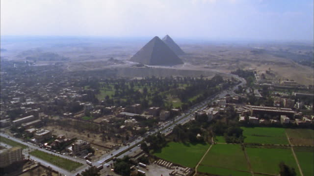aerial wide shot giza pyramids and downtown cityscape / cairo, egypt - pyramide bauwerk stock-videos und b-roll-filmmaterial