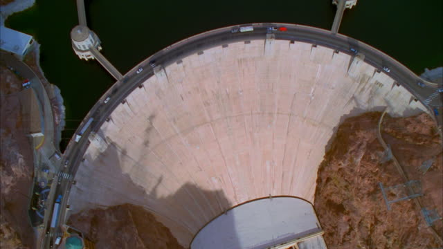 vídeos de stock, filmes e b-roll de aerial wide shot hoover dam/ pan overhead traffic moving over dam/ pan colorado river/ nevada and arizona - represa hoover