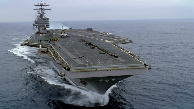 Aerial wide shot hull of USS Carl Vinson sailing through Pacific / long shot above ship with F-14 Tomcat on deck