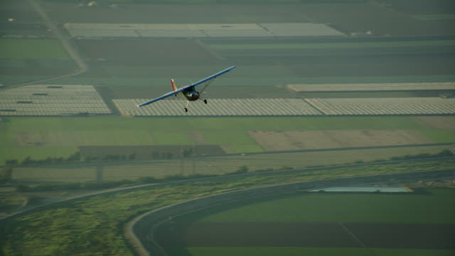 Aerial wide shot of polished metal Cessna 140 aircraft flying in warm backlight, with farm fields in the BG, California, in late afternoon.