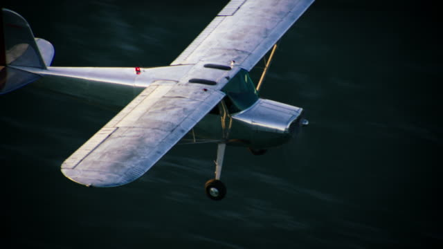 Aerial wide shot of polished metal Cessna 140 aircraft flying in warm backlight, with the Pacific Ocean in the BG, California, in late afternoon.