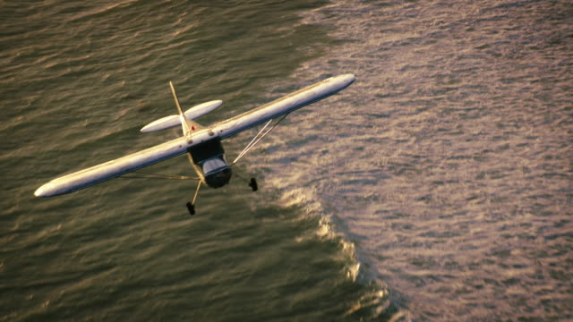 Aerial wide shot of polished metal Cessna 140 aircraft flying in warm backlight, with sun glittering off the Pacific Ocean in the BG, California, in late afternoon.