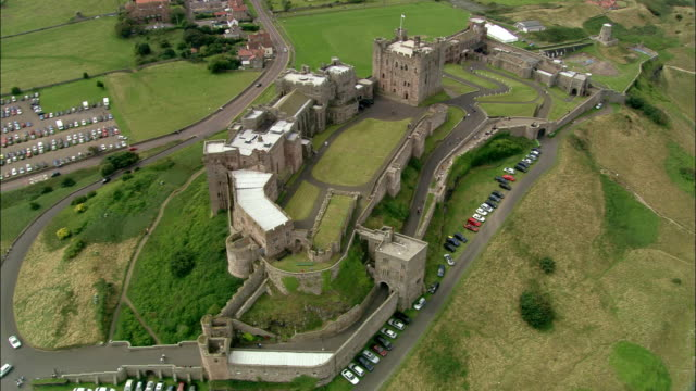 aerial wide shot over bamburgh castle / long shot view of castle on northumberland coastline / bamburgh, england - northumberland coast stock videos & royalty-free footage