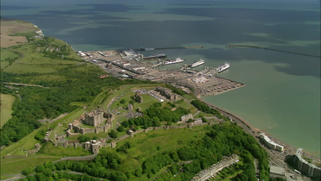 vidéos et rushes de aerial wide shot over dover castle and dover harbour with english channel in background / kent, england - xiième siècle