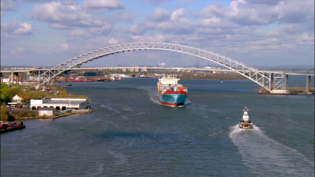 aerial wide shot pan container ship passing under bayonne bridge/ bayonne, new jersey - staten island stock videos and b-roll footage