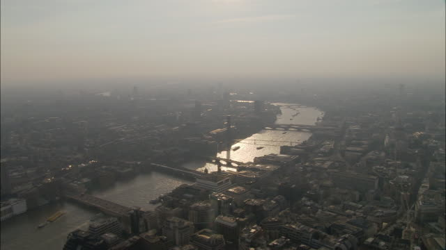 aerial wide shot pan foggy, backlit london cityscape looking west up the thames / england - smog stock videos & royalty-free footage