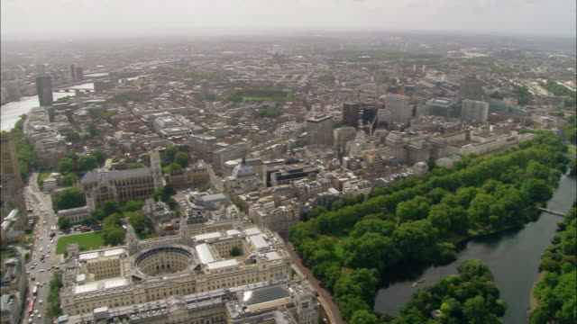 Aerial wide shot pan from Thames and Westminster to Buckingham Palace / London, England